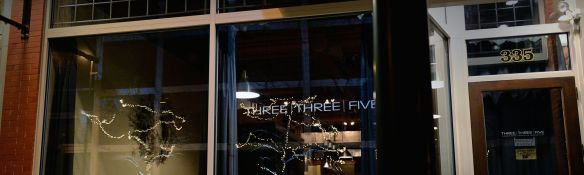 THREE I THREE I FIVE with Christmas lights reflected in window