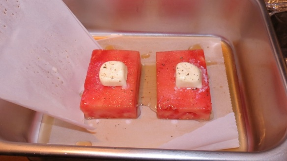 "Watermelon ""steaks"" seasoned with salt and pepper and a pat of butter and ready for the oven"